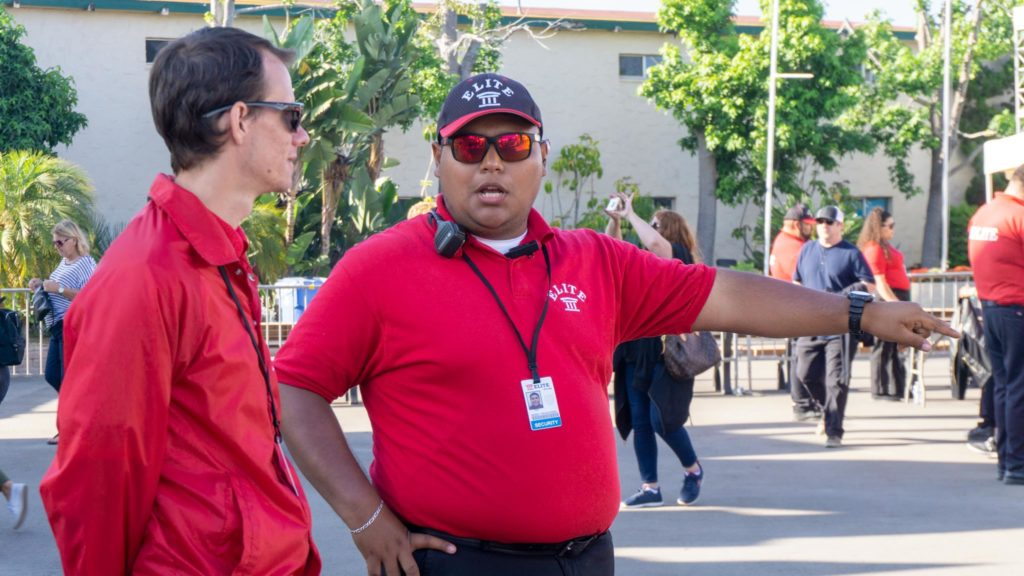 Two security guards working outdoors at the entrance to the San Diego County Fair