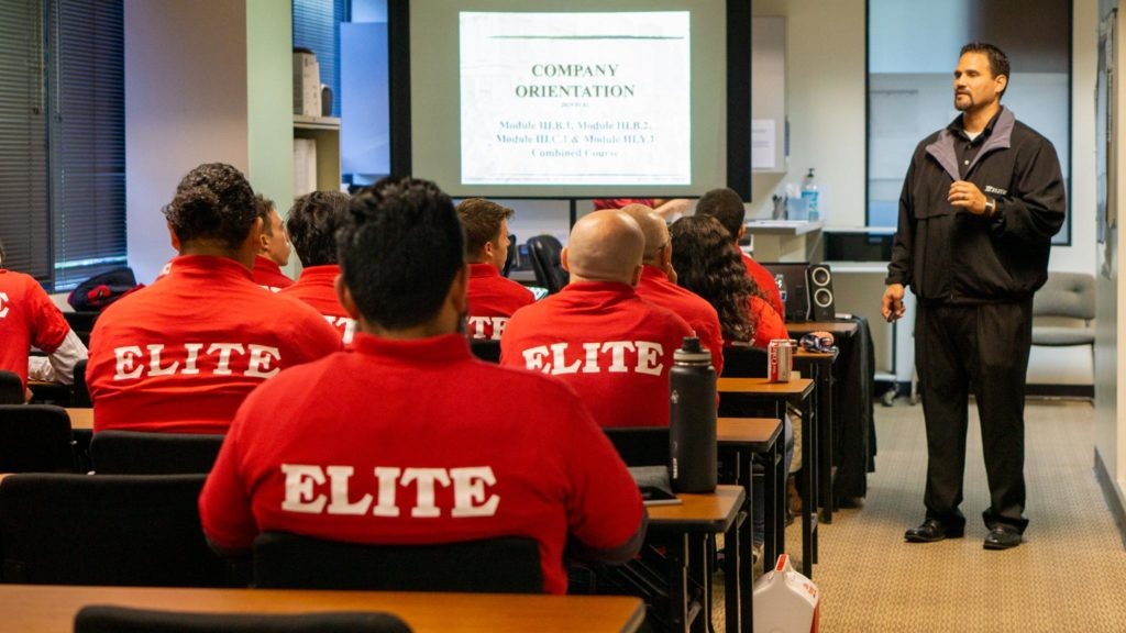 Training and Certification Class with new Elite employees in red polo shirts listening to orientation instruction