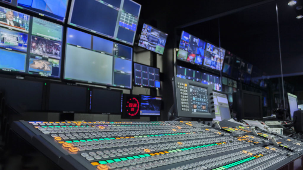Broadcast media production room with switching boards and audio controls
