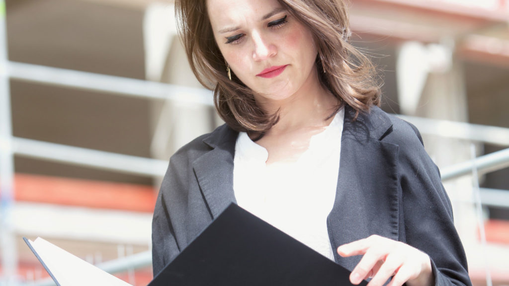 Woman performing on-site security audit with notebook